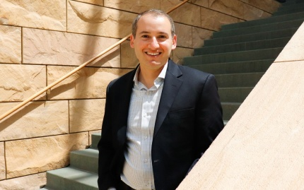 Prof. Jeremy Kress stands on stairs smiling outside Michigan Ross